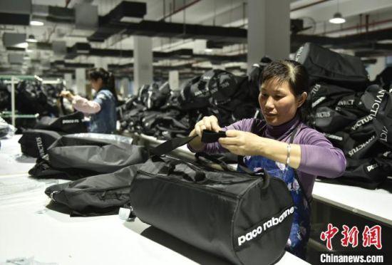在蓝山县皮具箱包科技产业园,工人在对休闲包进行整理、打包。 杨雄春 摄