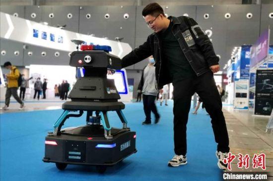 展会现场,一名观众与安防巡逻机器人打招呼。 龙腾 摄