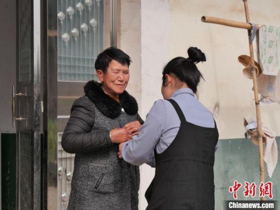 苏萌给罗翠英拍照前为其整理衣服。 王昊昊 摄