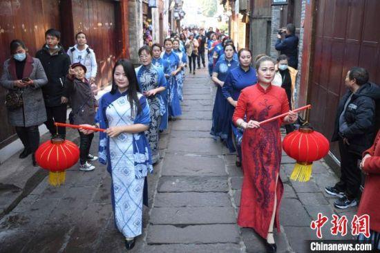 湖南凤凰古城的民俗巡游吸引游人驻足欣赏。 杨华峰 摄