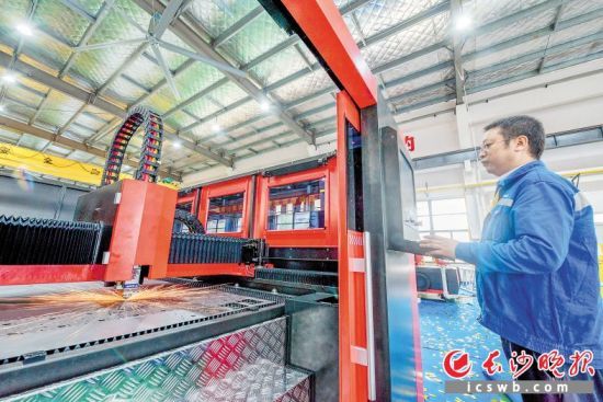 湖南大族智能装备制造基地的生产车间内,产业工人加紧对激光加工设备进行组装和调试。  陈飞 摄
