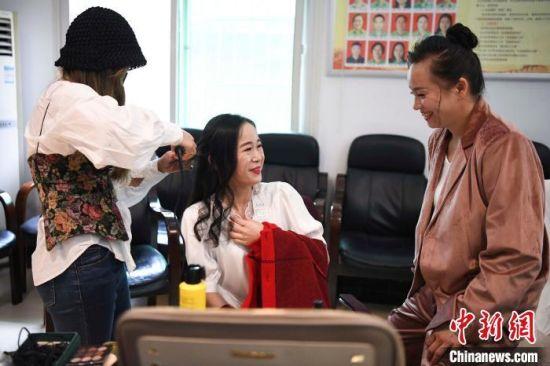 很少化妆的女工人们在化妆台前交流。 杨华峰 摄
