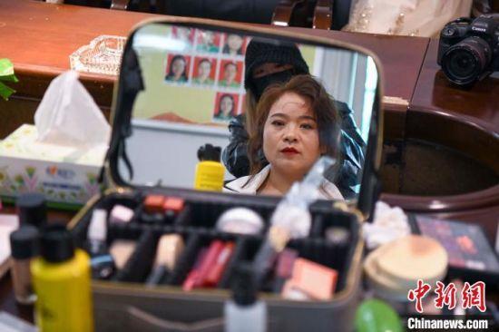 化妆师为女工人化妆。 杨华峰 摄