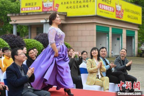 女工人身着礼服在T台上走秀。 杨华峰 摄