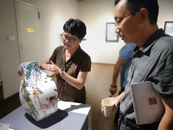"""""""关兰・瓷彩2021""""11日下午在长沙开展,关兰(左)介绍作品。 刘曼 摄"""