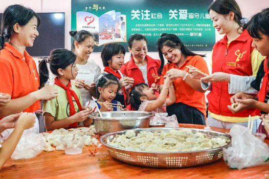 志愿者教学生包饺子。