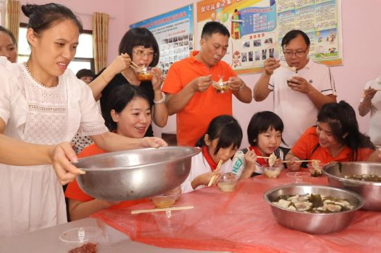 志愿者和学生们一起吃饺子。