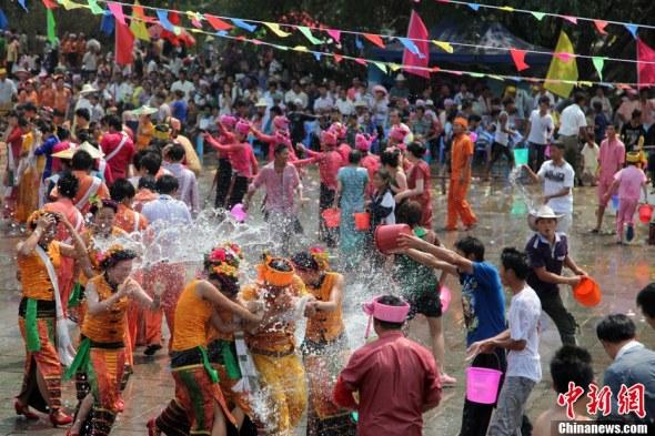 ...傣族、德昂族传统的泼水节.图为游客与当地少数民族一共泼水...