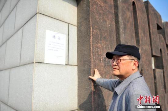沈阳/3月27日,康明在沈阳抗美援朝烈士陵园外抚摸陵园标示。
