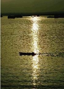 殷建军/夕阳照在洞庭湖上,一条小船飞快地驶过湖面。图/殷建军