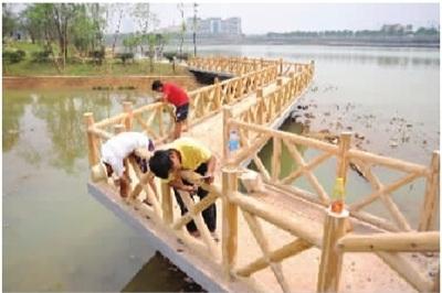 几名工作人员在给木质护栏刷油漆